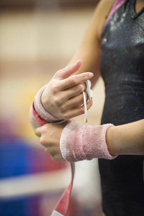 Female gymnast wrapping wrists in preparation, croppedの写真素材 [FYI04322307]