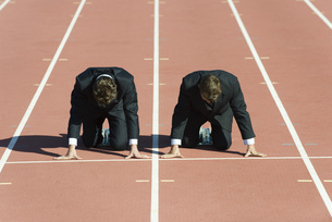 Businessmen crouched in starting position on running trackの写真素材 [FYI04322309]