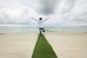 Man standing on one leg at end of carpet on beach with armsの写真素材 [FYI04322323]