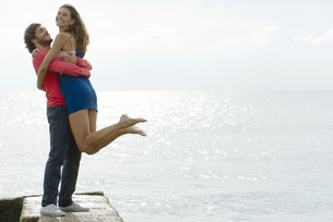 Young man lifting girlfriend up by water, portraitの写真素材 [FYI04322326]
