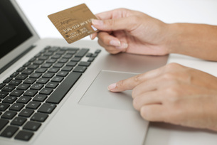 Woman holding credit card while using laptop computer, croppの写真素材 [FYI04322347]