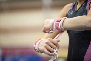 Female gymnast wrapping wrists in preparation, croppedの写真素材 [FYI04322350]