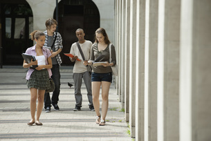 University students walking on campus discussing schoolworkの写真素材 [FYI04322372]