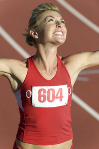 Woman running on track, looking up victoriouslyの写真素材 [FYI04322375]