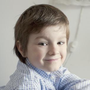 Boy smiling over shoulder, portraitの写真素材 [FYI04322380]