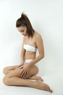 Woman in underwear touching her legの写真素材 [FYI04322382]