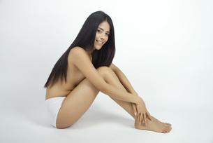 Young woman sitting in underwear, hugging knees, portraitの写真素材 [FYI04322389]