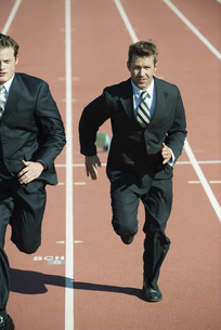 Businessmen racing each other on running trackの写真素材 [FYI04322391]