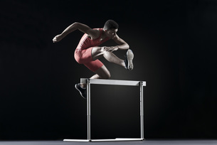 Male athlete clearing hurdleの写真素材 [FYI04322392]
