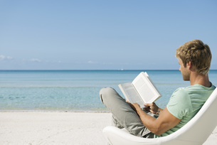 Young man reading book on beachの写真素材 [FYI04322399]