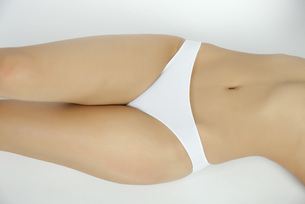 Woman lying on back in underwear, mid sectionの写真素材 [FYI04322400]