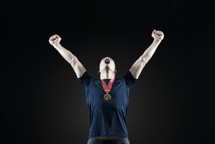 Male athlete shouting with arms raised in victoryの写真素材 [FYI04322402]