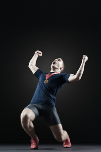 Male athlete shouting with arms raised in victoryの写真素材 [FYI04322406]