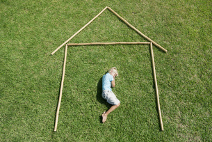 Boy lying on grass within outline of house, high angle viewの写真素材 [FYI04322408]