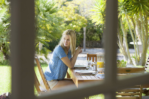 Woman sitting at outdoor table, gazing over shoulderの写真素材 [FYI04322428]