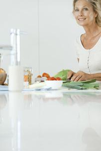Mature woman preparing healthy meal, smiling at cameraの写真素材 [FYI04322430]