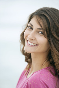 Young woman smiling over shoulder, portraitの写真素材 [FYI04322434]
