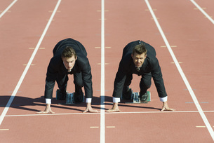 Businessmen crouched in starting position on running trackの写真素材 [FYI04322467]