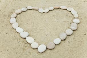 Pebbles arranged in heart shape on sandの写真素材 [FYI04322507]