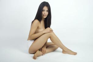 Woman sitting in underwear, full length portraitの写真素材 [FYI04322529]