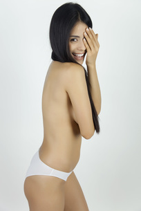 Woman in underwear covering one eye and smiling at camera, pの写真素材 [FYI04322537]