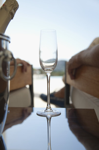 Champagne flute, people relaxing in backgroundの写真素材 [FYI04322542]