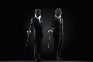 Businessmen standing with fencing masks and foilsの写真素材 [FYI04322556]