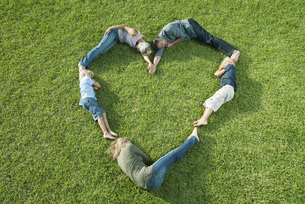 People lying on grass positioned in shape of heartの写真素材 [FYI04322569]