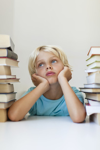 Boy sitting between two stacks of books, daydreamingの写真素材 [FYI04322577]