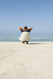 Man sitting in armchair on beach looking at ocean, rear viewの写真素材 [FYI04322590]