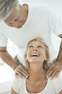 Mature couple smiling at each other as man massages woman'sの写真素材 [FYI04322594]