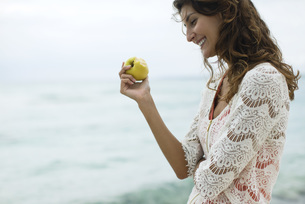 Woman eating apple at the beachの写真素材 [FYI04322618]