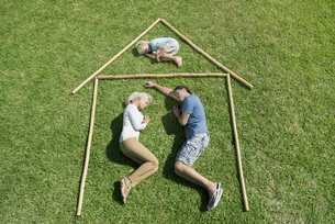 Family with one child lying on grass within outline of houseの写真素材 [FYI04322677]