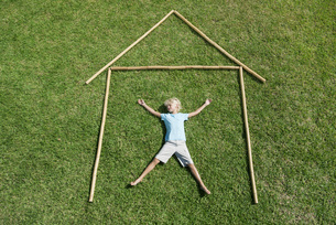 Boy lying on grass within outline of house, high angle viewの写真素材 [FYI04322678]