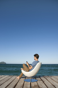 Young man sitting in armchair by lake using cell phone, sideの写真素材 [FYI04322713]