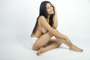 Woman sitting in underwear, full length portraitの写真素材 [FYI04322714]