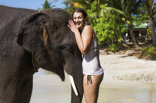 Portrait of smiling woman embracing elephant on sea shoreの写真素材 [FYI04322731]
