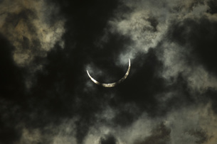Low angle view of crescent moon in cloudy sky at nightの写真素材 [FYI04322737]