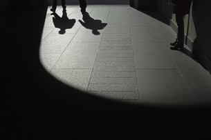 Low section of people in shadow on sidewalkの写真素材 [FYI04322792]