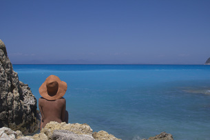 Rear view of woman relaxing on rocky sea shore against clear blue skyの写真素材 [FYI04322817]