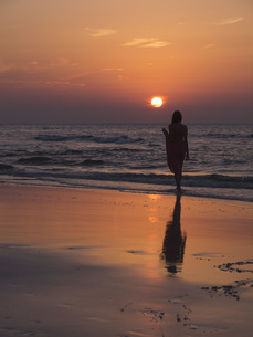 Full length of woman standing on beach against sky during sunsetの写真素材 [FYI04322819]