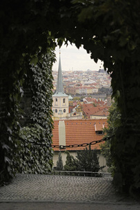View of church and city seen through ivy covered archway, Prague, Czech Republicの写真素材 [FYI04322825]