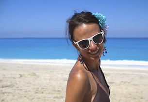 Beautiful woman smiling and wearing sunglasses at beachの写真素材 [FYI04322829]