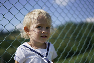 Cute toddler standing against chainlink fenceの写真素材 [FYI04322835]