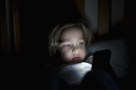 Young boy using mobile phone while lying on bed at nightの写真素材 [FYI04322839]