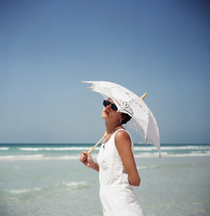 Portrait of a woman holding a parasol and standing on a beachの写真素材 [FYI04322840]