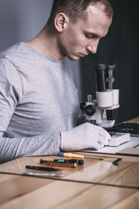 Young male technician examining circuit board with microscope at electronics storeの写真素材 [FYI04322848]