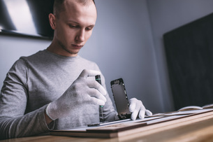 Young male technician repairing smart phone at electronics storeの写真素材 [FYI04322850]