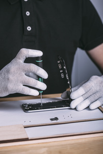 Midsection of technician repairing mobile phone at electronics storeの写真素材 [FYI04322867]