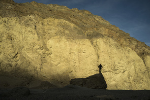 Silhouette of man standing on rock against mountain, Death Valley, Nevada, USAの写真素材 [FYI04322870]